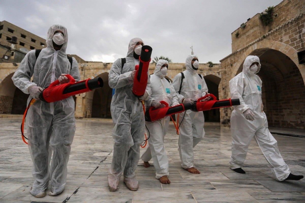 Trabalhadores palestinas desinfectam lugares de culto como medida preventiva diante de receios da propagação do coronavírus, 12 de março de 2020 [Ashraf Amra/Apaimages]