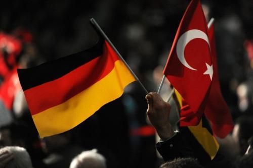Um visitante segura uma bandeira turca e alemã durante um evento cultural turco na Alemanha em 27 de fevereiro de 2011 [ Patrik Stollarz/ AFP/ Getty Images]