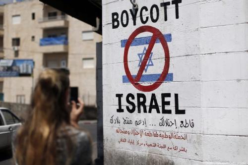 Turista fotografa uma placa pintada em uma parede na cidade de Belém, na Cisjordânia, em 5 de junho de 2015, chamando a boicotar produtos provenientes de assentamentos israelenses [Thomas Coex/ AFP / Getty Images]