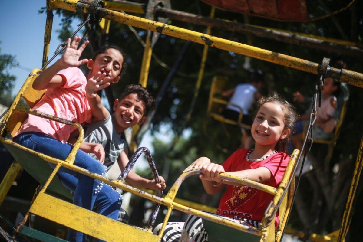 Crianças palestinas desfrutam das festividades do Eid al-Adha, em um playground em Rafah, Faixa de Gaza, 1° de agosto de 2020 [Mustafa Hassouna/Agência Anadolu]
