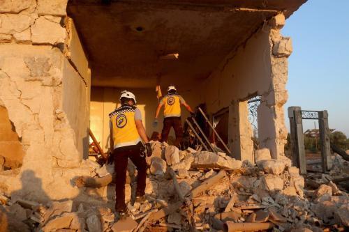 Trabalhadores da defesa civil realizam uma busca e operação de resgate no local após aviões de guerra pertencentes ao regime de Assad e à Rússia terem realizado ataques aéreos na cidade de Binnish, Idlib, no noroeste da Síria, em 3 de agosto de 2020 [Asaad Al Asaad / Agência Anadolu]