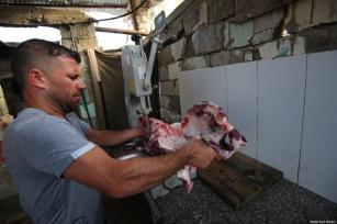 Palestinos em Gaza observam o corte da carne para distribuição, como parte do sacrifício Eid ul Adha Qurbani, em 31 de julho de 2020 [Mohammad Asad / Monitor do Oriente Médio]