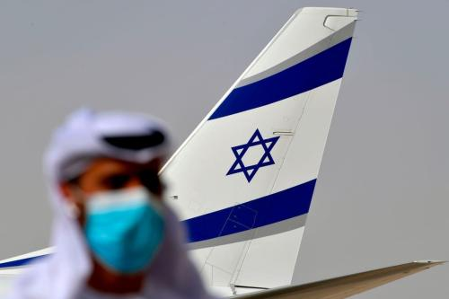 Oficial emiradense ao lado de avião da El Al, após primeiro voo comercial realizado entre Israel e Emirados Árabes Unidos, 31 de agosto de 2020 [Karim Sahib/AFP/Getty Images]