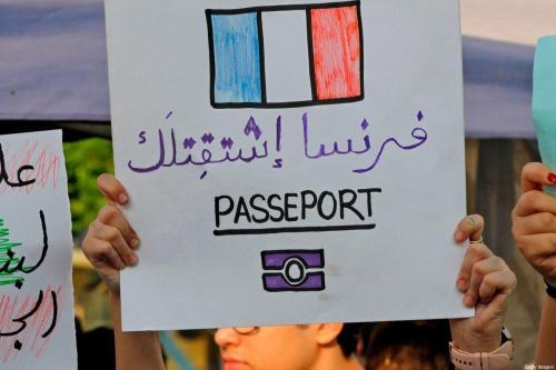 Manifestantes libaneses exibem cartazes em árabe: 'França, sentimos saudades' [Mahmoud Zayyat/AFP/Getty Images]