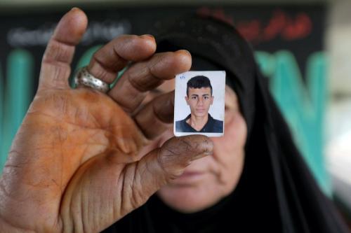 Mulher iraquiana exibe uma foto de seu filho, com quem perdeu, durante protestos contra o governo na Ponte Siniq, em Bagdá, capital do Iraque, 24 de novembro de 2019 [Sabah Arar/AFP/Getty Images]