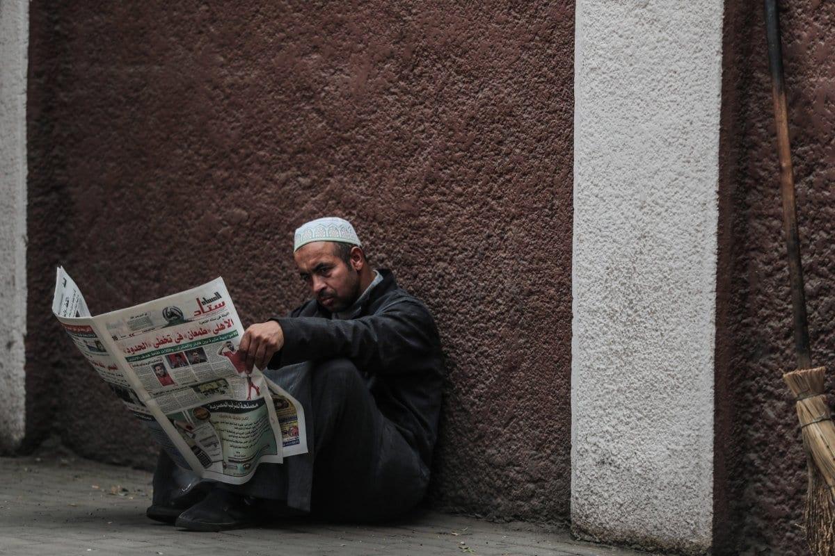 Um homem lê jornal em calçada do Cairo, Egito, 15 de dezembro de 2019 [MOHAMED EL-SHAHED / AFP / Getty Images].