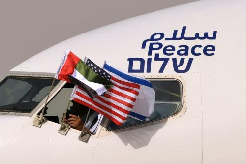 Bandeiras dos Emirados Árabes Unidos, Estados Unidos e Israel são expostas na janela de um avião da companhia israelense El Al, adornado com a palavra 'paz' em árabe, inglês e hebraico, durante o primeiro voo comercial entre Israel e Abu Dhabi, 31 de agosto de 2020 [Karim Sahib/AFP/Getty Images]