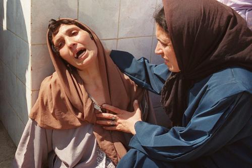 Uma mulher desesperada, que mais tarde foi chamada de 'Madonna de Bentalha' é consolada por um parente no hospital Zmirli após ter perdido toda a sua família, em 23 de setembro de 1997 [Hocine Zaourar/ AFP via Getty Images]