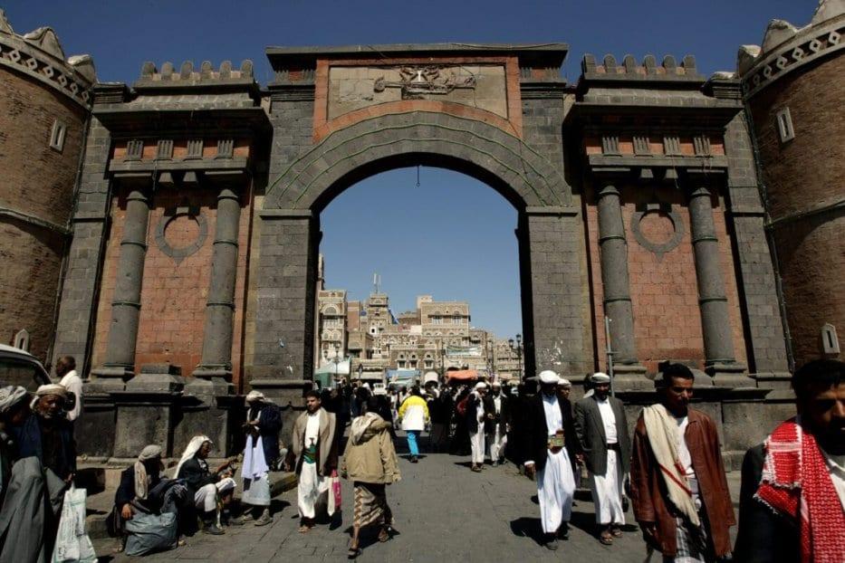 Os iemenitas passam sob o icônico Portão do Iêmen, que leva à cidade velha de Sanaa em 8 de novembro de 2009 [MARWAN NAAMANI / AFP via Getty Images]