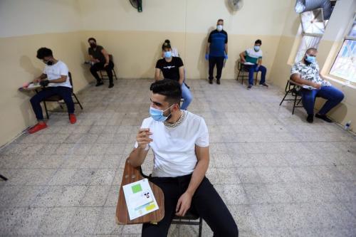 Estudantes iraquianos, usando máscaras protetoras, mantém distanciamento social enquanto fazem seus exames finais, em meio a medidas contra o coronavírus (COVID-19). Bagdá, Iraque, 01 de setembro de 2020 [Murtadha Al-Sudani - Agência Anadolu].