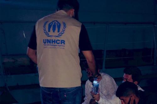 Um trabalhador do ACNUR com requerentes de asilo que estavam no mar, 22 de setembro de 2020 [UNHCRLibya / Twitter]