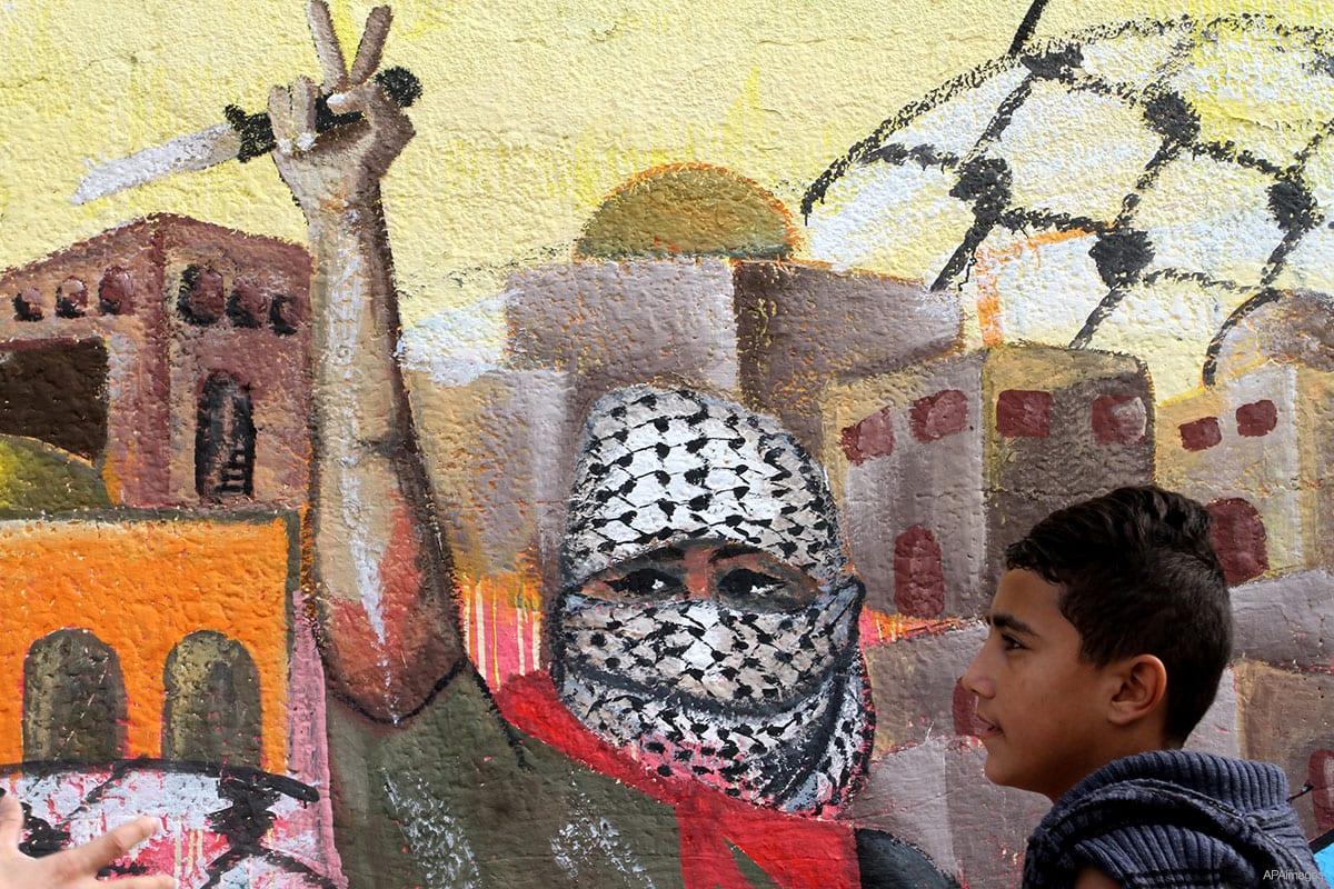 Menino palestino caminha em frente a um mural em apoio à Intifada de Jerusalém [foto de arquivo]