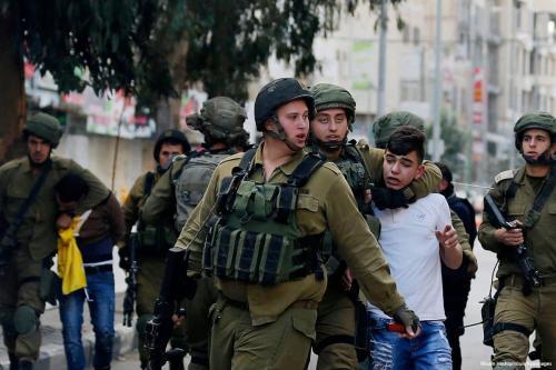 Solados israelenses prendem um menor palestino na Cisjordânia em 20 de dezembro de 2017 [Wisam Hashlamoun / Apaimages]