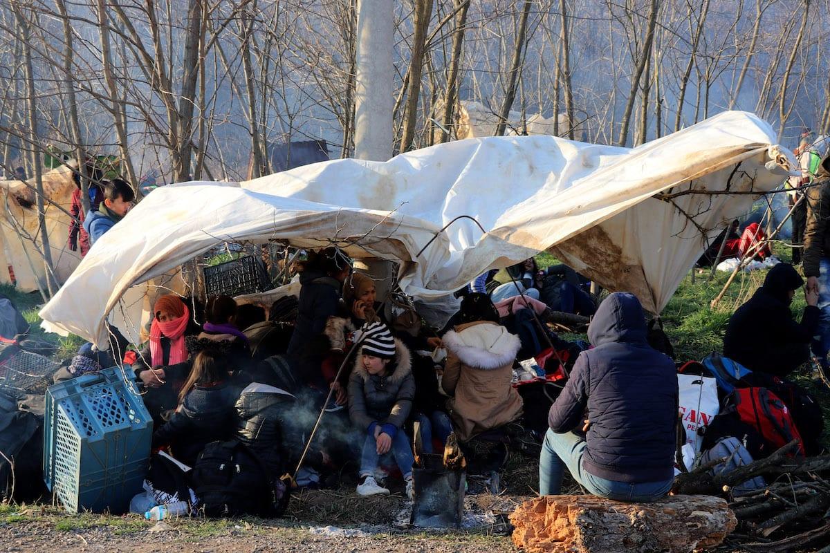 Refugiados que querem atravessar à Europa aguardam do lado turco da zona neutra, entre os portões de Kastanies (Grécia) e Pazarkule (Turquia), em 29 de fevereiro de 2020 [Cihan Demirci/Agência Anadolu]