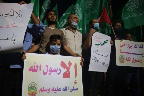 Palestinos protestam contra a reimpressão de caricaturas do Profeta Muhammad, consideradas ofensivas, por uma publicação francesa, em Rafah, Faixa de Gaza, 24 de outubro de 2020 [Mustafa Hassona/Agência Anadolu]