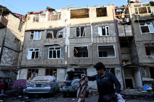 Mulher carrega seus pertences para fora de um edifício danificado por recentes bombardeios, em Stepanaker, principal cidade da região disputada de Nagorno-Karabakh, 3 de outubro de 2020 [AFP/Getty Images]