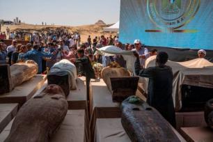 Trabalhadores egípcios cobrem os sarcófagos escavados pela missão arqueológica do Egito, expostos em coletiva de imprensa na Necrópole de Saqqara, 3 de outubro de 2020 [Khaled Desouki/AFP/Getty Images]