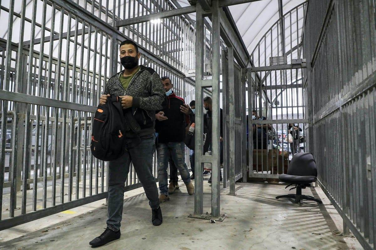 Palestinos que trabalham em Israel passam pelo posto de controle Tarqumia ao norte de Hebron, na Cisjordânia ocupada, ao entrarem em Israel, usando máscaras devido ao coronavírus, em 4 de outubro de 2020. (Foto de Hazem Bader/ AFP via Getty Images)