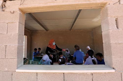 Estudantes palestinos sentam-se com seu professor dentro de uma sala de aula na escola Ras al-Tenneen no leste da cidade de Ramallah, que um tribunal israelense decidiu que foi construída sem a licença de construção necessária e rejeitou um recurso contra sua demolição iminente, em 8 de outubro de 2020. [Abbas Momani/ AFP via Getty Images]