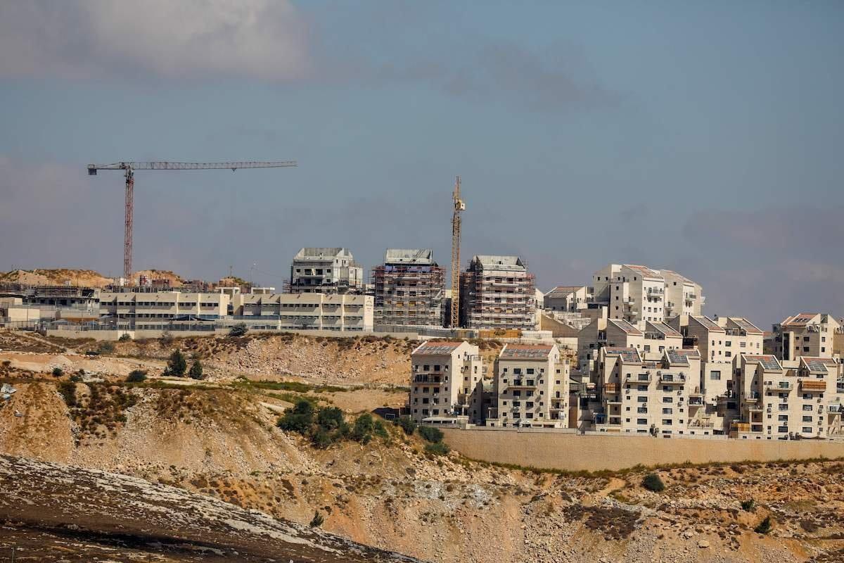 Guindastes israelenses em um canteiro de novas unidades habitacionais no assentamento judeu de Kochav Yaakov, perto da cidade palestina de Ramallah, na Cisjordânia ocupada, em 14 de outubro de 2020. [Ahmad Gharabli/ AFP/Getty Images]