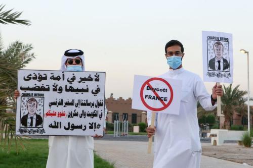 Kuwaitianos levantam cartazes contra o presidente francês Emmanuel Macron na Cidade do Kuwait, em 24 de outubro de 2020 [AFP/ Getty Images]