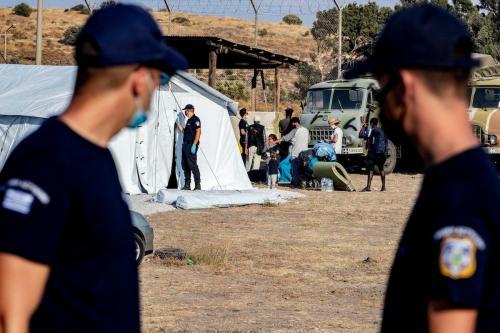 Agentes da ACNUR observam migrantes durante a transferência para o novo campo de refugiados, em 12 de setembro de 2020 em Lesbos, Grécia. [Niels Wenstedt/ BSR Agency/ Getty Images]