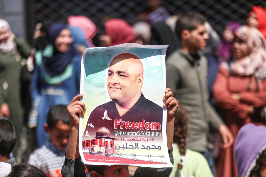 Manifestantes palestinos exibem cartazes com a imagem de Mohammed Al-Halabi, em Gaza, 28 de março de 2017 [Mustafa Hassona/Agência Anadolu]