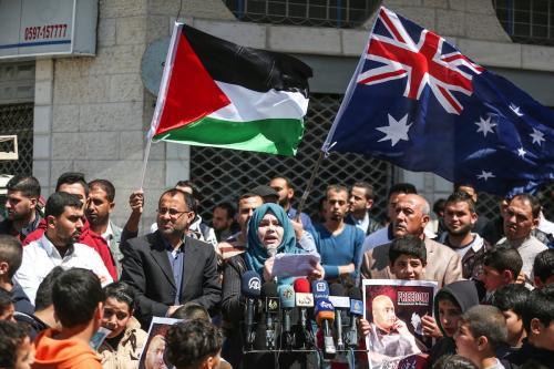Tehani Zakkut discursa a manifestantes palestinos que exibem cartazes de Mohammad El Halabi, diretor de operações da Visão Mundial Internacional para a Faixa de Gaza, preso por forças israelenses, em ato de 28 de março de 2017 [Mustafa Hassona/Agência Anadolu]