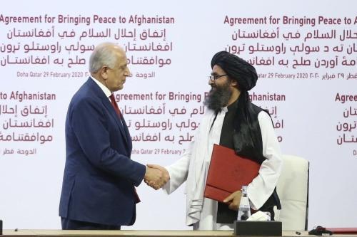 Zalmay Khalizad (à esquerda), representante especial dos Estados Unidos para reconciliação no Afeganistão, e Mullah Abdul Ghani Baradar, cofundador do Talibã, apertam as mãos após assinatura de um acordo de paz, em Doha, Catar, 29 de fevereiro de 2020 [Fatih Aktas/Agência Anadolu]