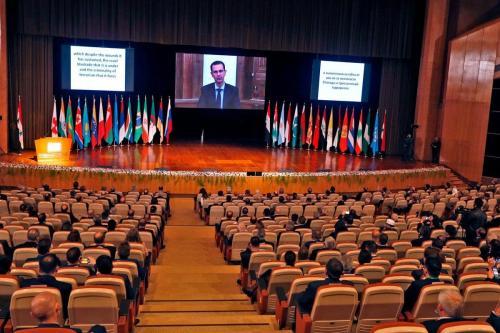 O presidente da Síria, Bashar Al-Assad (na tela) na conferência internacional sobre o retorno dos refugiados detidos em Damasco, em 11 de novembro de 2020 [Loual Beshara/ AFP / Getty Images]