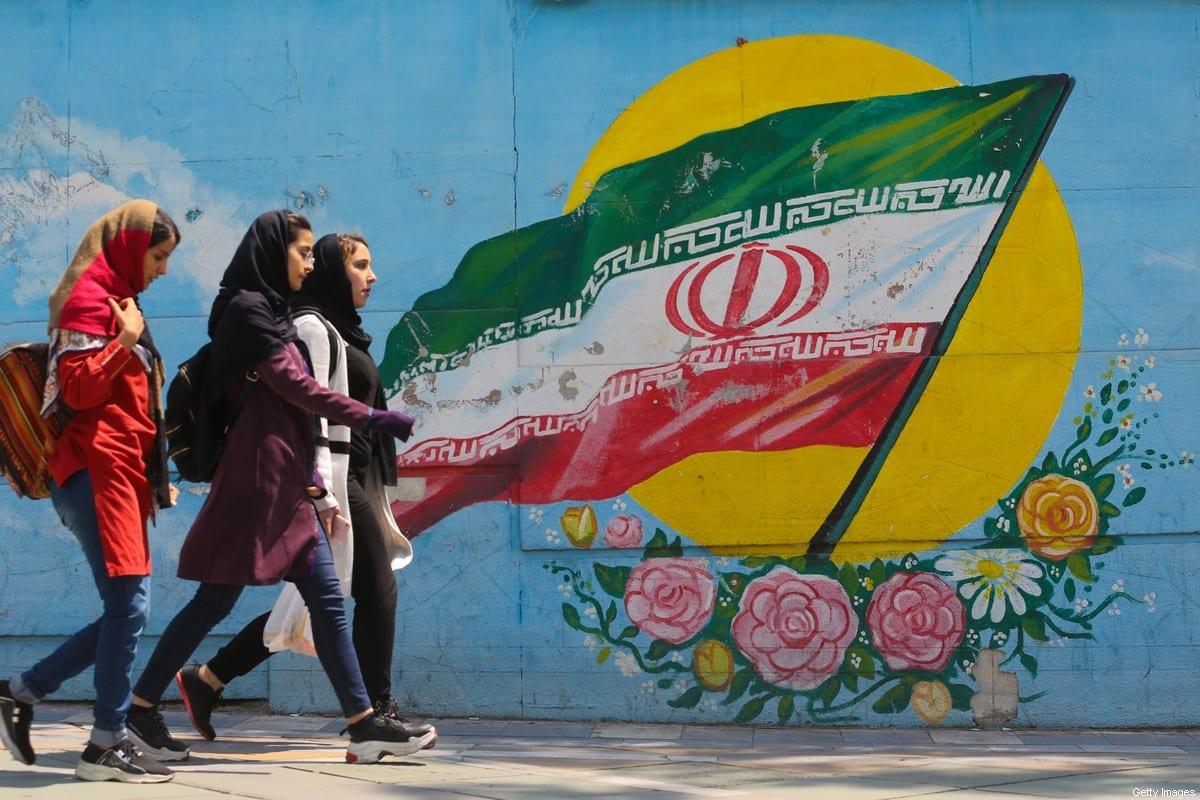 Jovens iranianas caminhas em frente a um mural com a bandeira nacional, no centro de Teerã, capital do Irã, 23 de abril de 2019 [Atta Kenare/AFP/Getty Images]