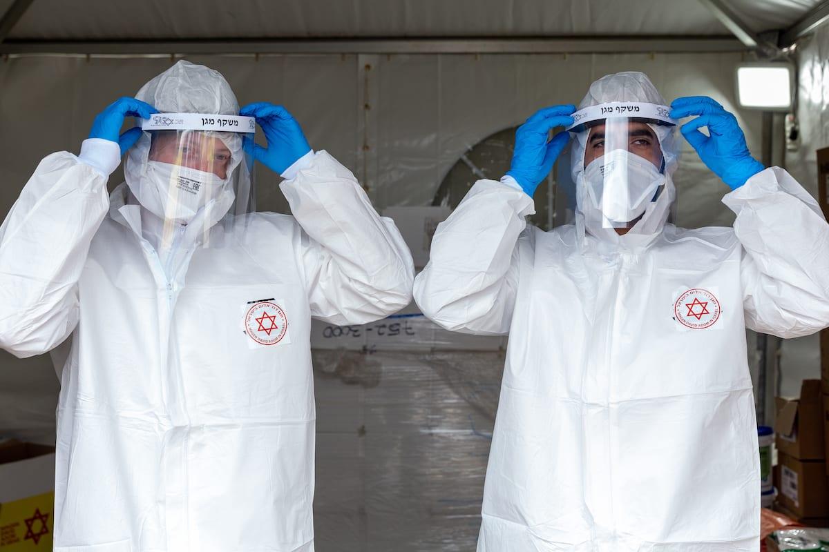 Equipes médicas vestem roupas de proteção para conduzir testes de coronavírus em um posto móvel, em Tel Aviv, 1° de abril de 2020 [Guy Prives/Getty Images]