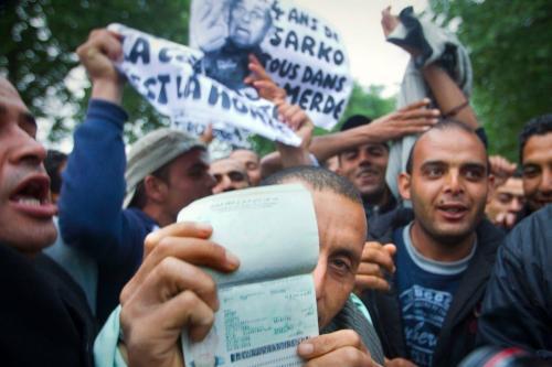 Um cidadão tunisino mostra seu passaporte em Paris, durante uma manifestação para protestar contra a política do Estado francês em relação aos migrantes tunisianos em 28 de abril de 2011 [Joel Saget / AFP / Getty Images]