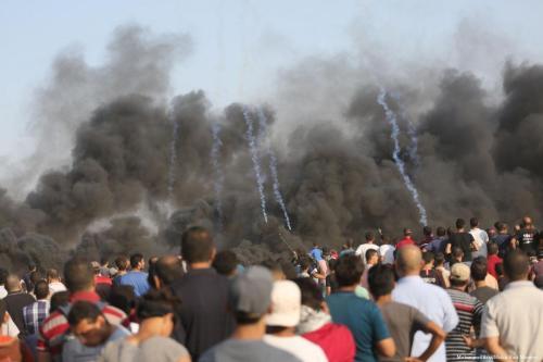 Forças israelenses atiram gás lacrimogêneo contra civis palestinos durante a Grande Marcha do Retorno, em 30 de setembro de 2018 [Mohammed Asad/Monitor do Oriente Médio]
