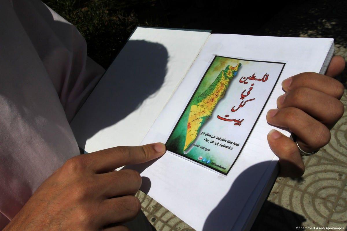 Um homem palestino com um mapa da Palestina na cidade de Gaza, 20 de junho de 2013 [Mohammed Asad / Apaimages]