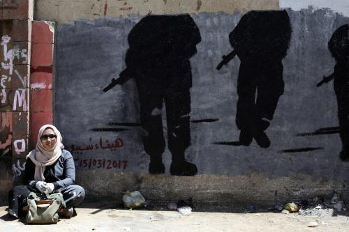 Mulher sentada em frente a uma parede com pinturas de silhuetas segurando rifles em Sanaa, Iêmen, em 15 de março de 2017. [Agência Mohammed Hamoud/Anadolu]