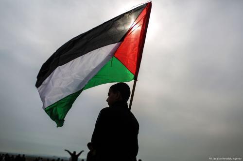 Menino palestino com uma bandeira palestina, em 29 de dezembro de 2017 [Ali Jadallah/Agência Anadolu]