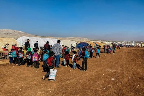 Crianças em fila para assistir aulas em tendas instaladas no campo de refugiados de Reyyan, na aldeia de Kafr Uruq, Idlib, Síria, 24 de novembro de 2020 [Muhammed Abdullah/Agência Anadolu]