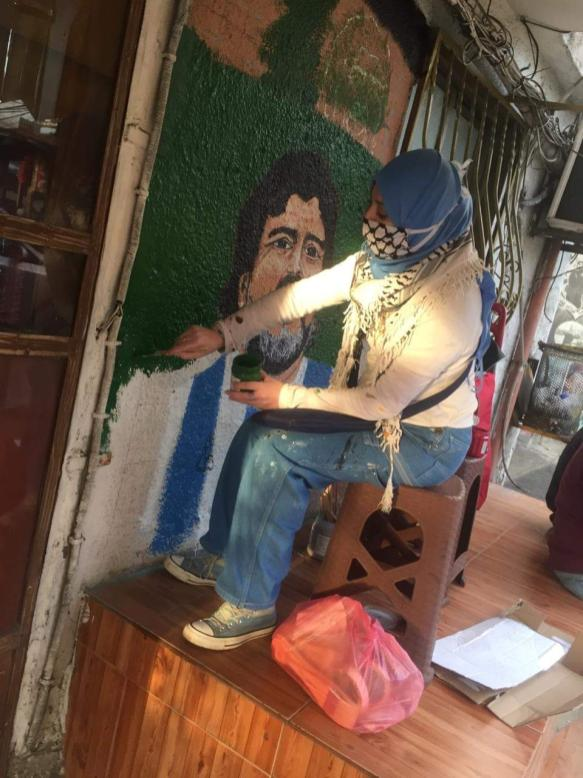 A pintora Tania Naboulsi enquanto pinta o mural [Cortesia para o Monitor do Oriente Médio]