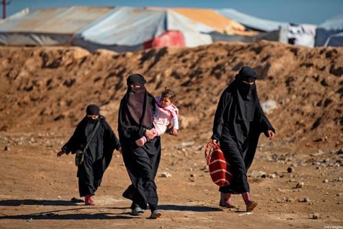Mulheres e crianças passam por um acampamento onde famílias de combatentes estrangeiros do Daesh são mantidos na Síria em 14 de janeiro de 2020 [Delil Souleiman/ AFP / Getty Images]