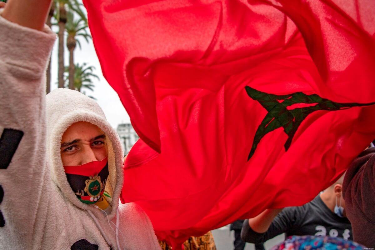 Marroquinos celebram em frente ao parlamento em Rabat em 13 de dezembro de 2020, depois que os EUA adotaram um novo mapa oficial do Marrocos que inclui o território disputado do Saara Ocidental [Fadel Senna/ AFP via Getty Images]