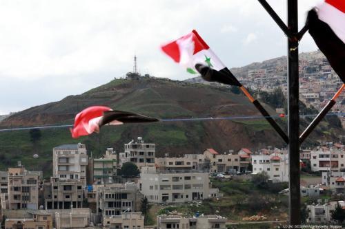 Bandeiras nacionais da Síria são hasteadas na cidade síria de Ain Al-Tineh no território das Colinas de Golan anexado por Israel. Em 26 de março de 2019 [Loua Beshara/ AFP / Getty Images]