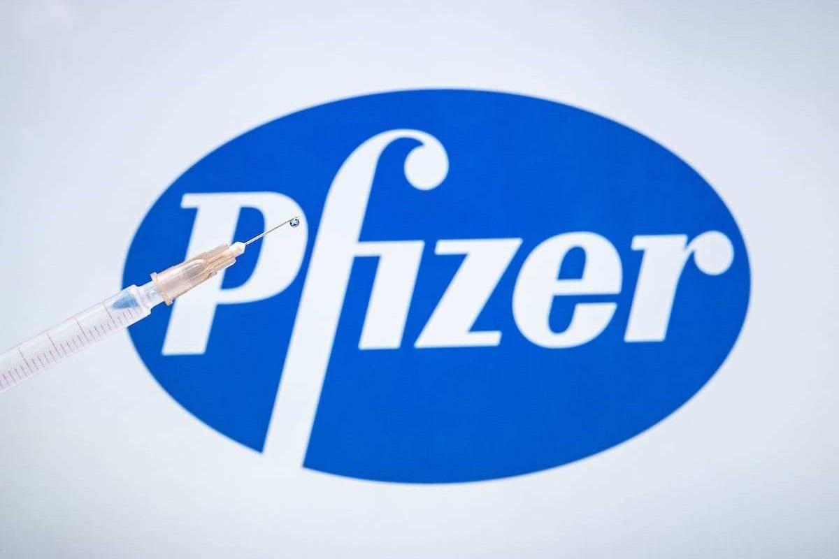 O logotipo da vacina Pfizer para covid-19 é exibido em uma tela com uma seringa na frente [Ali Balıkçı / Agência Anadolu]