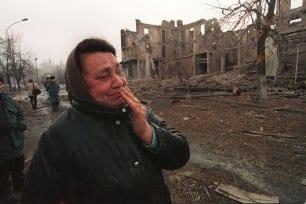 Mulher chechena chora ao passar por edifícios destruídos pela guerra entre tropas russas e separatistas, em Grosny, Chechênia, 28 de dezembro de 1994 [Hector Mata/AFP/Getty Images]