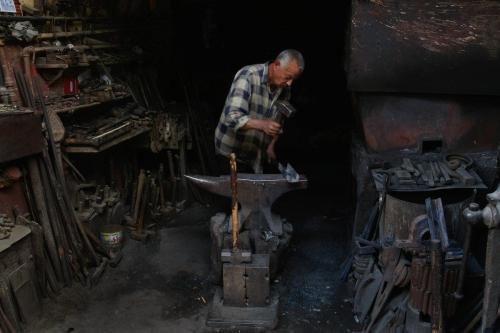 Um ferreiro egípcio martela em uma oficina de aço quente no Cairo, Egito. [David Silverman/Getty Images]