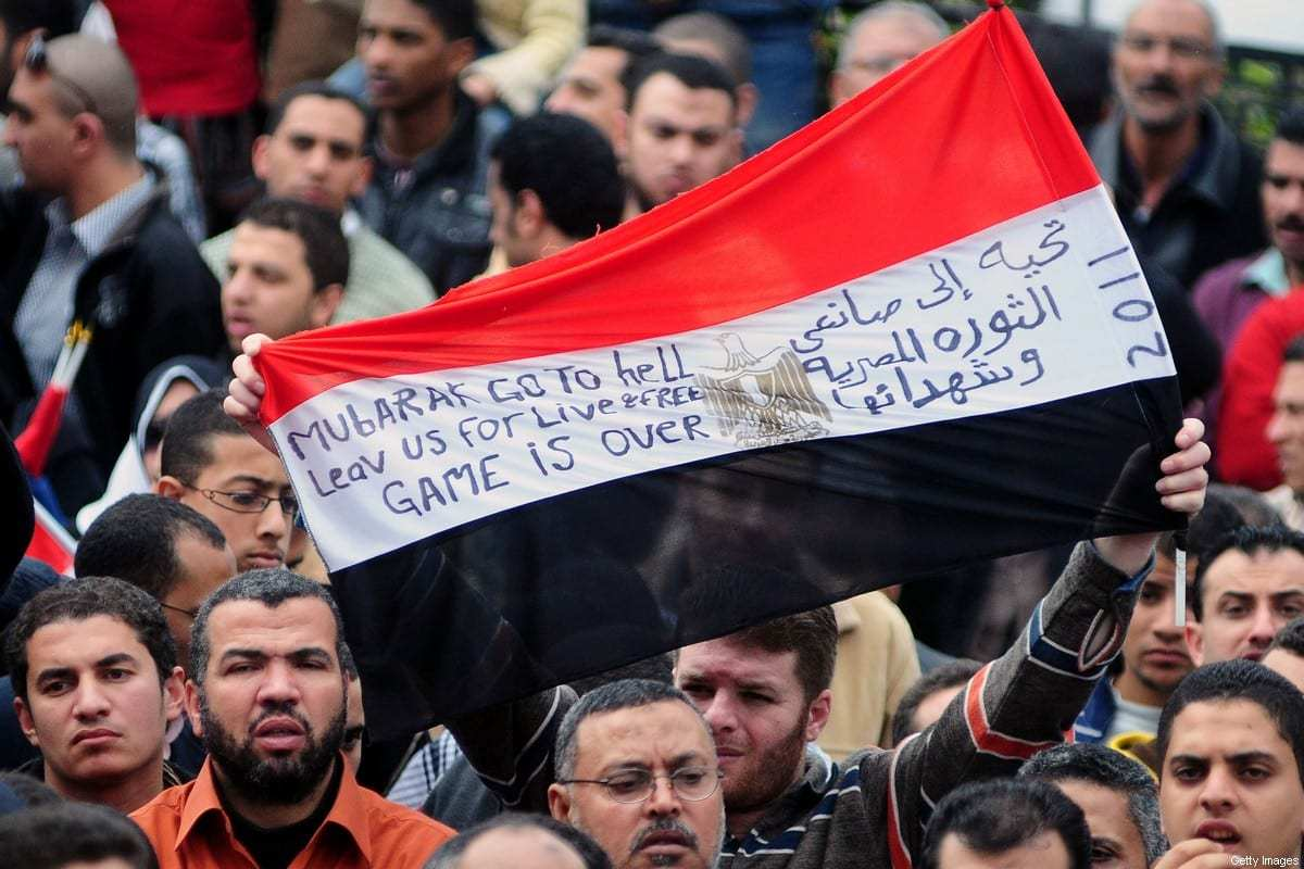 """Um manifestante antigovernamental egípcio segura sua bandeira nacional com a inscrição em árabe """"Uma saudação aos criadores da revolução egípcia e seus mártires"""", em Alexandria, em 6 de fevereiro de 2011, no 13º dia de protestos pedindo a derrubada de presidente Hosni Mubarak. [AFP via Getty Images]"""