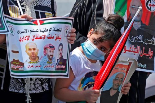Menina palestina com máscara de proteção contra o coronavírus exibe o retrato de um preso palestino durante protesto contra prisões arbitrárias de Israel, em frente ao Comitê Internacional da Cruz Vermelha, em Nablus, Cisjordânia ocupada, 26 de agosto de 2020 [Jafaar Ashtiyeh/AFP/Getty Images]