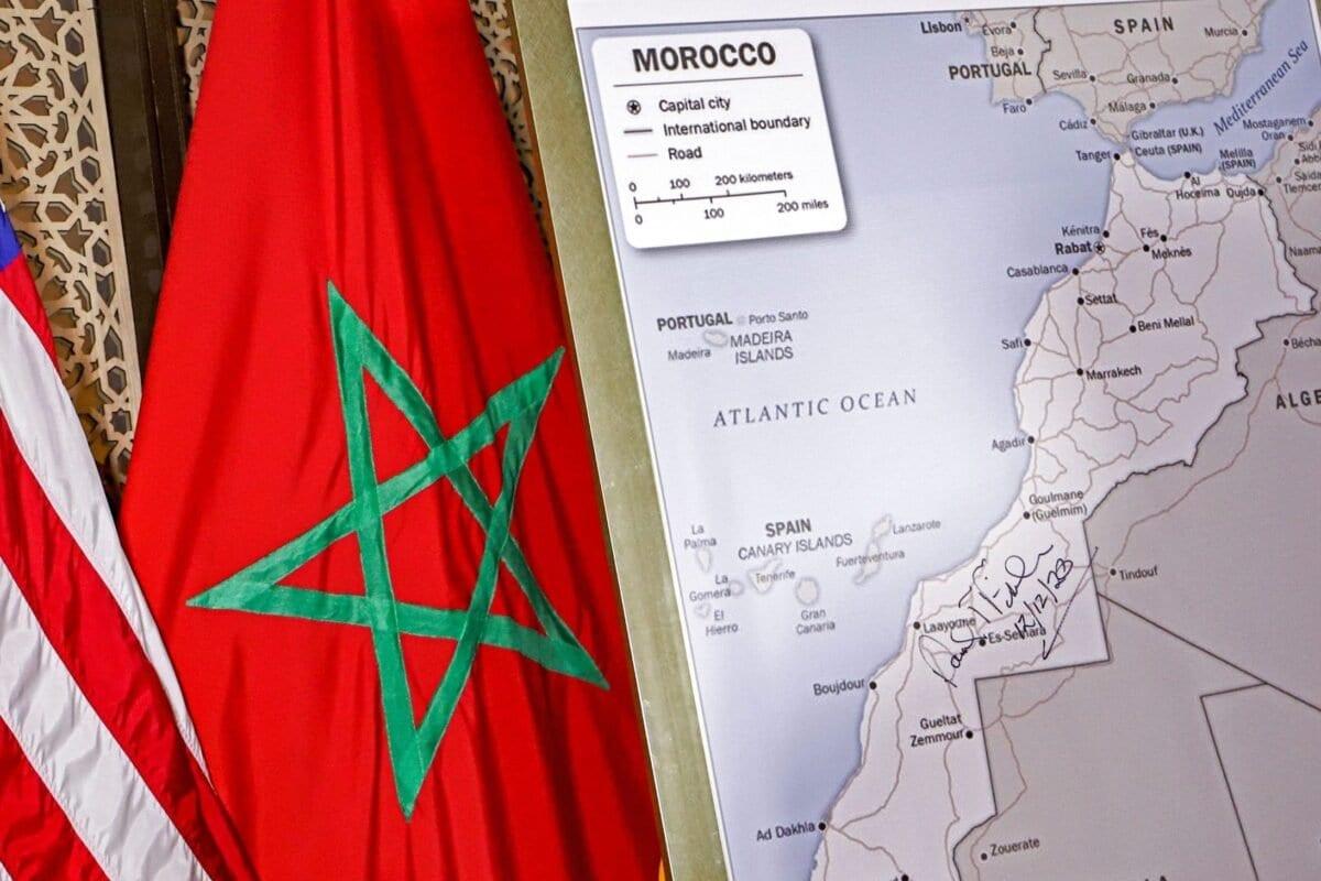 Foto tirada em 12 de dezembro de 2020 mostra (da esquerda para a direita) bandeiras dos EUA e do Marrocos ao lado de um mapa do Marrocos, autorizado pelo Departamento de Estado dos EUA, reconhecendo o território internacionalmente disputado do Saara Ocidental [AFP via Getty Images]