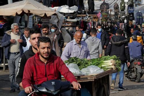 Libaneses, alguns usando máscaras de proteção devido à pandemia causada pela covid-19, fazem compras em um mercado no bairro de Sabra, em Beirute, em 6 de janeiro de 2021. [ANWAR AMRO/AFP via Getty Images]