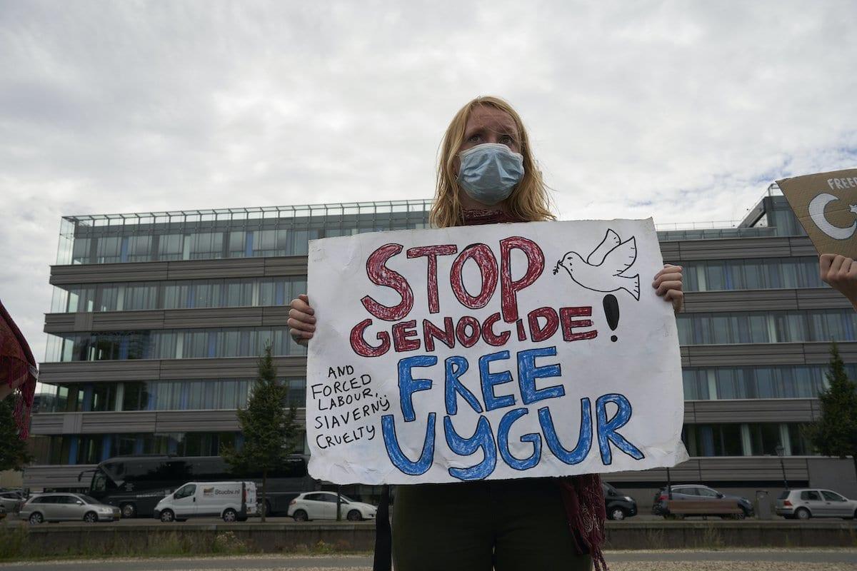 Manifestantes carregam cartazes com mensagens contra as políticas do governo chinês para o povo uigur, em 20 de agosto de 2020 em Haia, Holanda [Nacho Calonge / Getty Images]